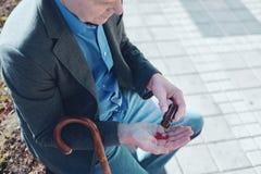 Schließen Sie oben vom älteren Mann, der draußen Pillen einnimmt lizenzfreies stockfoto