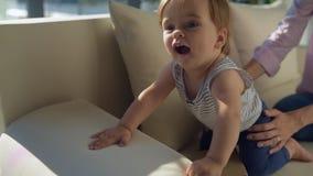 Schließen Sie oben vom aktiven Kind, das auf dem Sofa sitzt stock video footage