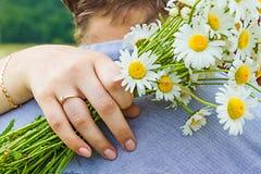 Schließen Sie oben vom Arm mit Blumenstraußkamille Lizenzfreie Stockfotos