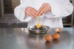 Schließen Sie oben vom Bäcker, der ein Ei in der Schüssel knackt Lizenzfreies Stockfoto