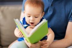 Schließen Sie oben vom Baby und vom Vater mit Buch zu Hause stockfoto
