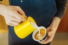 Schließen Sie oben vom barista, das gedämpfte Milch in die Kaffeetasse gießt, die Lattekunst macht lizenzfreies stockbild