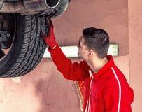Schließen Sie oben vom Bewegungsmechaniker, der die Suspendierung auf einem Auto überprüft Lizenzfreie Stockfotos