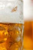 Schließen Sie oben vom Bierkrug, der mit Becher im Hintergrund vertial ist Lizenzfreie Stockfotos