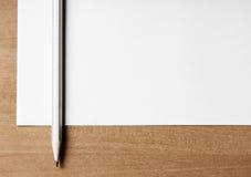 Schließen Sie oben vom Bleistift und vom leeren Papier auf einem Desktop Lizenzfreie Stockbilder