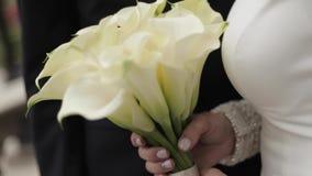 Schließen Sie oben vom Brautgriffblumenstrauß in den Händen stock video