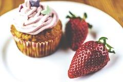 Schließen Sie oben vom Erdbeerrosakleinen kuchen auf weißer Platte auf hölzernem Hintergrund Lizenzfreies Stockfoto