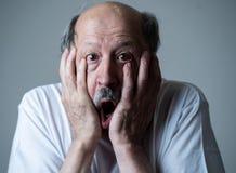 Schließen Sie oben vom erschrockenen und entsetzten älteren Mann, der in Furcht mit den Händen und Gesicht gestikuliert stockbild
