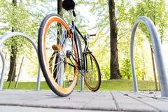 Schließen Sie oben vom Fahrrad, das am Straßenparken zugeschlossen wird Lizenzfreie Stockbilder