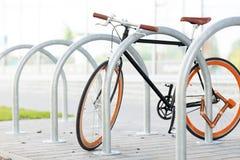 Schließen Sie oben vom Fahrrad, das am Straßenparken zugeschlossen wird Stockfotografie
