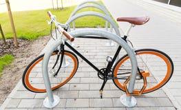 Schließen Sie oben vom Fahrrad, das am Straßenparken zugeschlossen wird Lizenzfreies Stockfoto