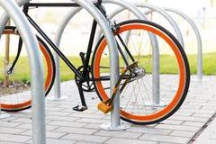 Schließen Sie oben vom Fahrrad, das am Straßenparken zugeschlossen wird Lizenzfreie Stockfotografie