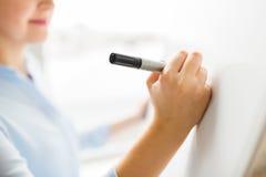 Schließen Sie oben vom Frauenschreiben etwas auf weißem Brett Lizenzfreies Stockbild