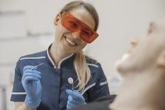Schließen Sie oben vom Frauenzahnarzt, der zu einem Kunden lächelt und zahnmedizinische Instrumente hält lizenzfreie stockbilder