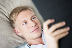 Schließen Sie oben vom freundlichen Mann, der ein Buch sich entspannt und liest. Lizenzfreies Stockfoto