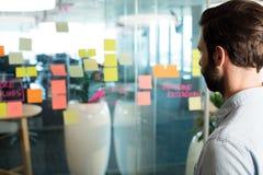 Schließen Sie oben vom Geschäftsmann, der klebende Anmerkungen und Strategie auf Glas betrachtet Stockfotografie