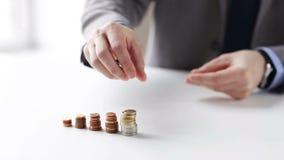 Schließen Sie oben vom Geschäftsmann, der Münzen in Spalten setzt stock video footage