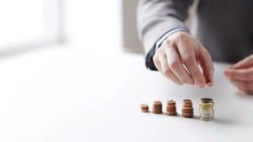 Schließen Sie oben vom Geschäftsmann, der Münzen in Spalten setzt stock video