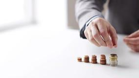 Schließen Sie oben vom Geschäftsmann, der Münzen in Spalten setzt stock footage