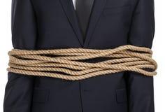 Schließen Sie oben vom Geschäftsmann, der mit dem Seil gebunden wird Lizenzfreie Stockfotos