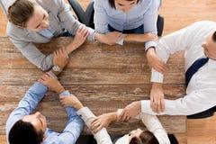 Schließen Sie oben vom Geschäftsteamhändchenhalten bei Tisch Lizenzfreies Stockfoto