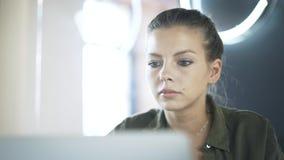 Schließen Sie oben vom Gesicht der jungen Frau s, das an ihrem Laptop arbeitet stock video footage