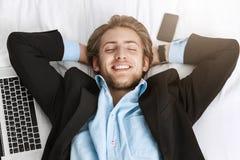 Schließen Sie oben vom glücklichen netten bärtigen Mann im schwarzen Anzug, der an zurück mit Laptop-Computer und Mobiltelefon na Stockbilder
