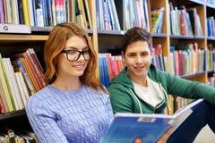 Schließen Sie oben vom glücklichen Studentenlesebuch in der Bibliothek stockfotos