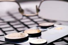 Schließen Sie oben vom goldenen Debet oder Kreditkarte, Brillen und Laptoptastatur mit Euromünzen Lizenzfreies Stockfoto