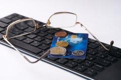 Schließen Sie oben vom goldenen Debet oder Kreditkarte, Brillen und Laptoptastatur mit Euromünzen Stockbild