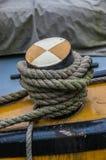Schließen Sie oben vom groben Seil, das um einen farbigen hölzernen Schiffspoller gebunden wird Stockbild