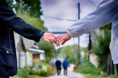 Schließen Sie oben vom Händchenhalten eines Paares stockfotografie
