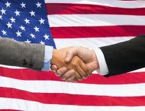 Schließen Sie oben vom Händedruck über amerikanischer Flagge Stockfotografie