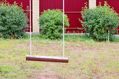 Schließen Sie oben vom hölzernen Schwingen mit Seil und grünen Büschen Lizenzfreie Stockfotografie