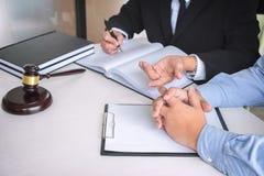Schließen Sie oben vom Hammer, vom männlichen Rechtsanwalt oder vom Richter Consult mit Kunden und stockfotografie