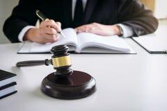 Schließen Sie oben vom Hammer, von männlichem Rechtsanwalt oder von Richter, die mit Gesetzbüchern arbeiten, lizenzfreie stockfotografie