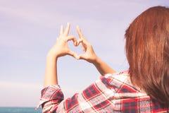 Schließen Sie oben vom Herzen, das durch Frauhandhintergrund der Türkisozean gemacht wird Lizenzfreie Stockbilder