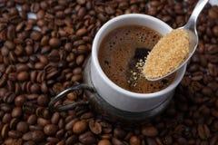 Schließen Sie oben vom Hinzufügen des braunen Zuckers im traditionellen türkischen Kaffee Stockfotografie