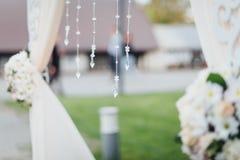Schließen Sie oben vom Hochzeitsdekor auf dem Bogen für die Hochzeitszeremonie, stockfotografie