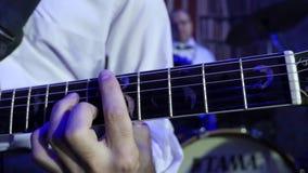 Schließen Sie oben vom Jazzgitarristen auf dem Stadium, welches die Galvanogitarre mit Vermittler spielt stock video