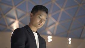 Schließen Sie oben vom jungen asiatischen Mann in der Jacke und im Hemd mit wechselwirkendem wayfinding Kiosk stock video footage