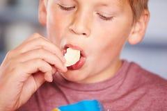 Schließen Sie oben vom Jungen, der Paket von Kartoffelchips isst Stockbild