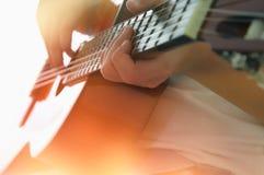Schließen Sie oben vom jungen Mädchen, das Akustikgitarre spielt lizenzfreie stockbilder