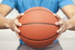 Schließen Sie oben vom jungen Mann, das Mittelteil und einen Basketball halten Lizenzfreie Stockbilder