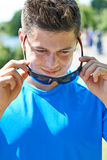 Schließen Sie oben vom jungen Mann, der in den Park läuft, der auf Sonnenbrille sich setzt stockfotos