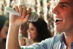Schließen Sie oben vom jungen Mann, der ein Mikrofon hält und am Karaoke, die Freunde singt, die im Hintergrund singen Stockbilder