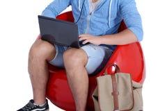 Schließen Sie oben vom jungen Mann, der im roten Puff unter Verwendung des Laptops sitzt Stockfotografie