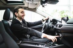 Schließen Sie oben vom jungen Mann in der Klage, die Auto fährt und irgendeinen Knopf auf Platte des Autos schaltet stockfotos