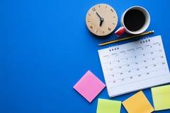 Schließen Sie oben vom Kalender, vom Kaffee, von der Uhr und vom Bleistift auf der blauen Tabelle lizenzfreie stockbilder