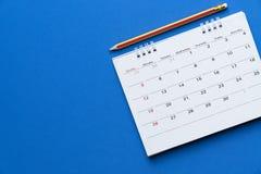 Schließen Sie oben vom Kalender und vom Bleistift auf dem blauen Hintergrund lizenzfreie stockfotografie